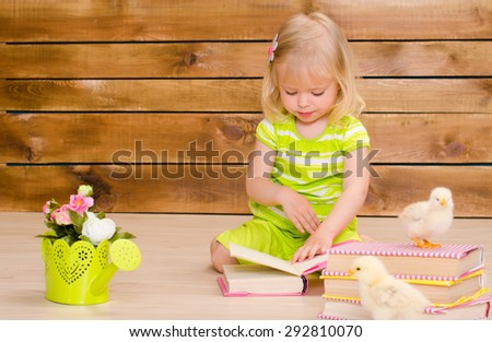 little blonde girl reading books and alive chickens on brown wooden wall background - stock photo