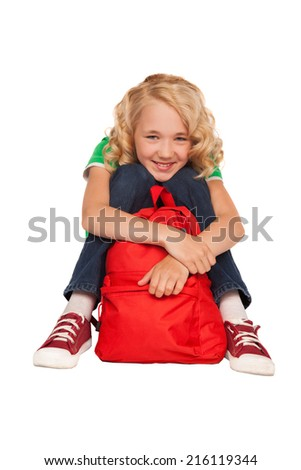 little blonde girl sitting on the floor near red bag over white background - stock photo