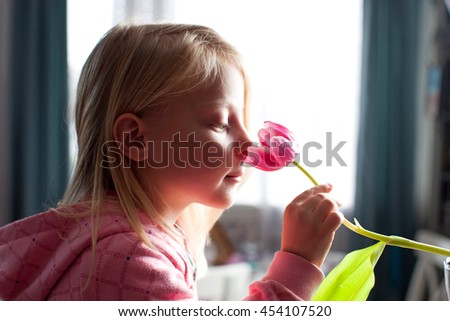 Little blonde girl smelling a tulip