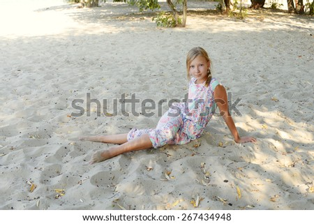 Little blonde girl teenager sits on the sand under the trees