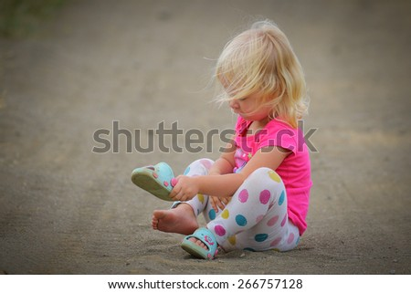 Little blonde girl wearing pink top on gravel road - stock photo