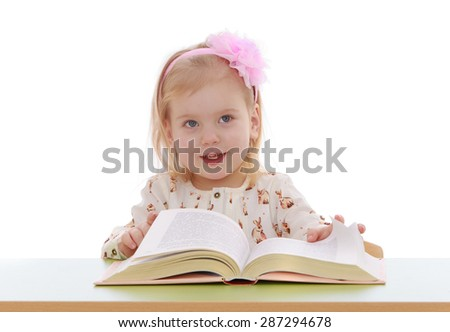 Little blonde girl with a bow on my head to read a book while sitting at table , close-up-Isolated on white background - stock photo