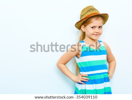 Little blonde girl with long hair posing on white background with straw hat. Studio portrait. - stock photo