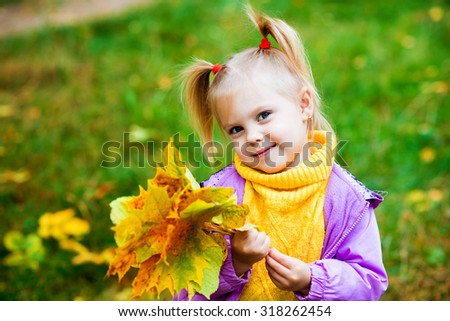 little blonde girl with pigtails cute sitting in autumn park