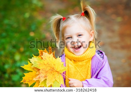 little blonde girl with pigtails in the autumn park with yellow