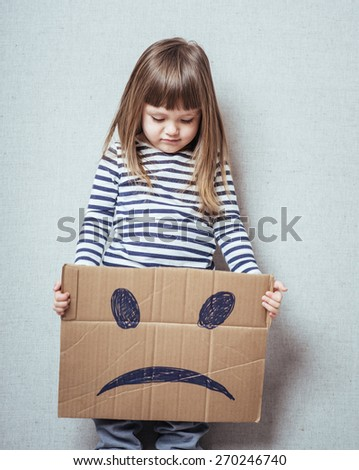 Little blonde girls holding sad face mask - stock photo