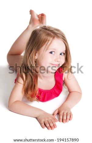 little blonde happy girl in pink swimsuit over white background lying on the floor  - stock photo