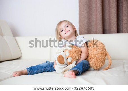 little blonde nice smiling girl three years sitting with a soft toy dog on a white leather couch