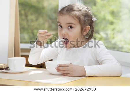 Little blonde preschooler girl eating delicious yogurt