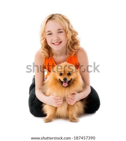 little blonde smiling girl holding her dog over white background - stock photo