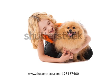 little blonde smiling girl holding her dog over white background - stock photo