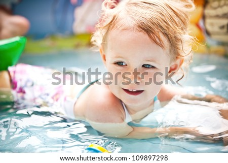 Little blondie girl in the swimming pool, soft focus - stock photo