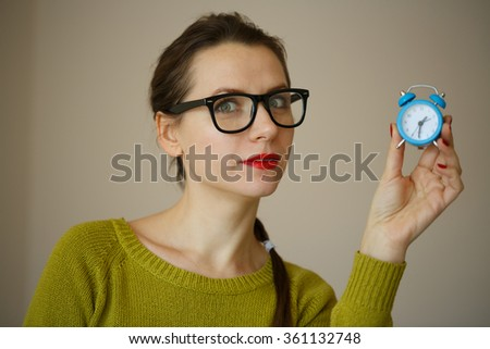 Little blue alarm clock in the hands of an emotional young woman, concept of saving time