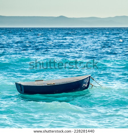 little blue boat is seesawing on waves in mediterranean - stock photo