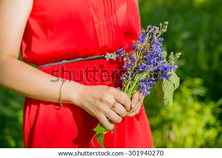 Little blue flower bouquet in female hand  - stock photo