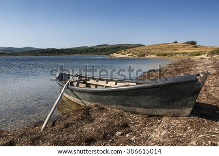 Little boat on the coast of a pond near Narbonne (Languedoc-Roussillon, France) at summer
