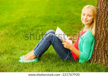 Little bookworm. Cute little blond hair girl holding book and smiling while sitting on green grass and leaning at the tree  - stock photo