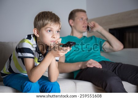 Little bored boy watching movie in living room - stock photo