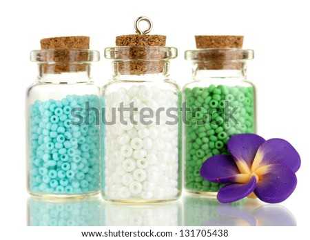 Little bottles full with colorful beads isolated on white - stock photo