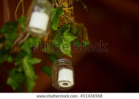 Little bottles with white candles hang from the green garland - stock photo