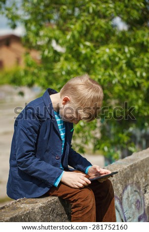 Little boy absorbed into his tablet for educating and playing.