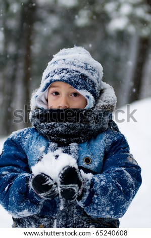 little boy  all bundled up in a snowsuit holding a snowball - stock photo