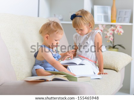 Little boy an girl sitting on the couch and reading books