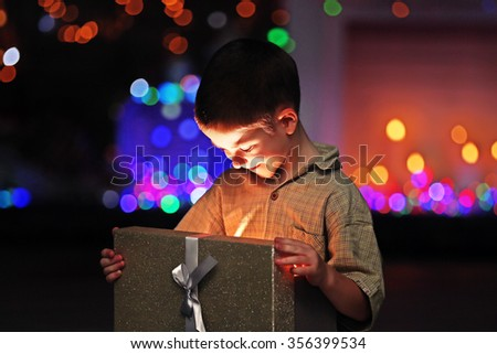 Little boy and a Christmas miracle from the box on a blurred dark background - stock photo