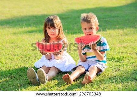 Little boy and a girl eating watermelon on a sunny day