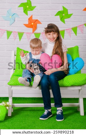 Little boy and an older sister smiling on the bench with the spring decor - stock photo