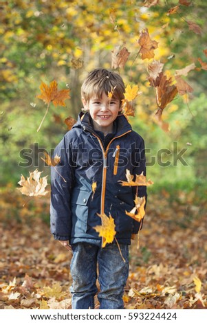 Little Boy and Autumn Leaves, outdoors in the woods smiling and having fun, soft light, vertical composition