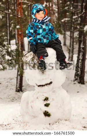 Little boy and big snowman in winter