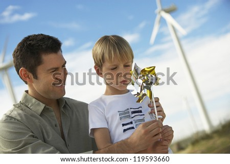 Little boy and father playing with paper windmill at windmill farm - stock photo