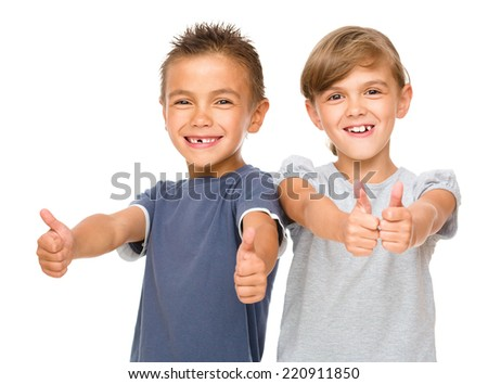 Little boy and girl are showing thumb up sign using both hands, isolated over white - stock photo