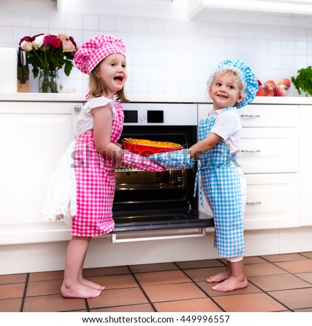 Little boy and girl, brother and sister baking delicious apple pie in white kitchen. Kids taking fruit cake out of oven. Children bake at home. Toddler child and preschooler kid cook for the family.