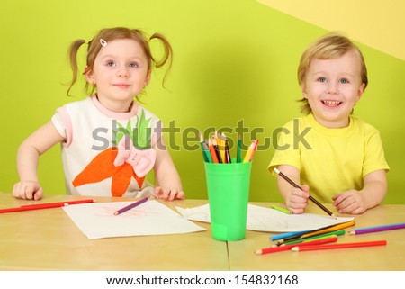Little boy and girl draw with colored pencils sitting at a table