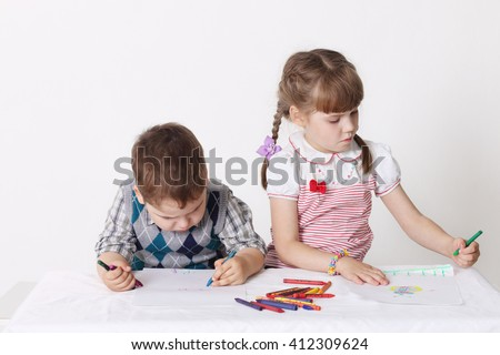 Little boy and girl draw with crayons sitting at table in studio