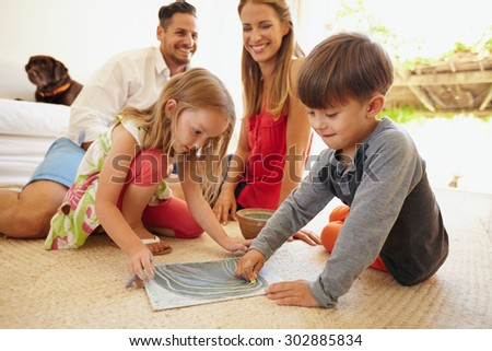 Little boy and girl drawing with chalk colors while sitting on floor. Children drawing with their parents in living room. - stock photo