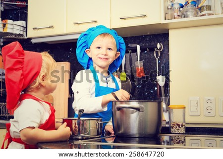 little boy and girl enjoy cooking in kitchen interior