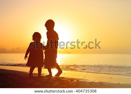 little boy and girl holding hands walking at sunset