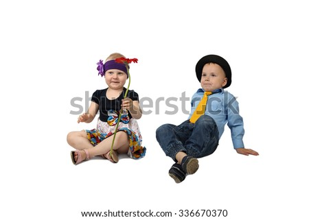 Little boy and girl in country style festive clothes sit on floor with flower in hands isolated on white background - stock photo