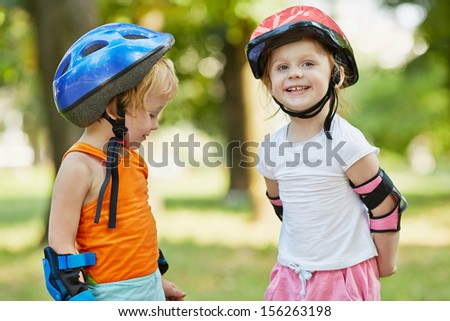 Little boy and girl in roller equipment stand together in summer park - stock photo
