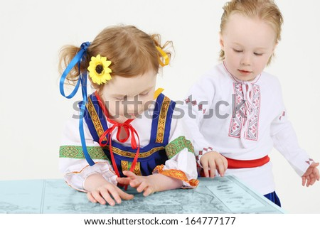 Little boy and girl in Russian national costume look at big map on white background.