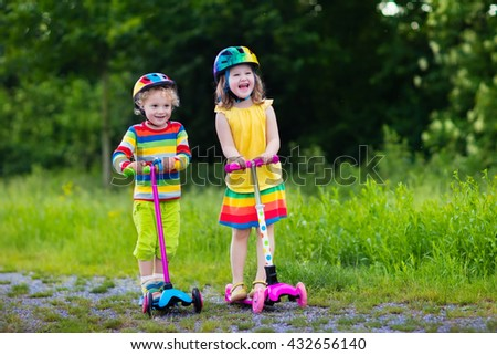 Little boy and girl in safety helmets with scooters. Child learning to ride a scooter in a park. Preschoolers riding a kick board. Kids play outdoors. Active leisure and outdoor sport for children. - stock photo
