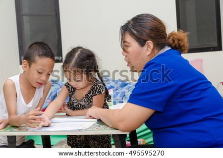 Little boy and girl learning at home with mom