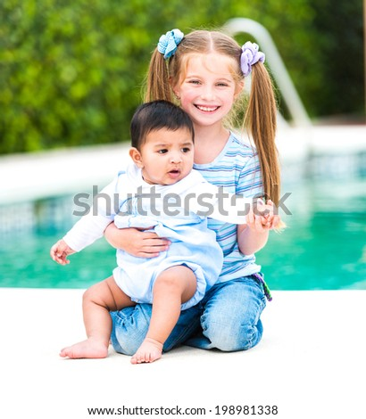 little boy and girl near the pool - stock photo