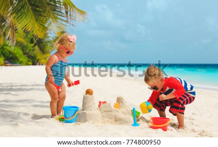 little boy and girl play with sand on beach