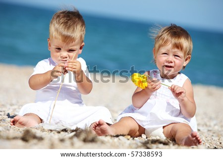 Little boy and girl playing by the sea in summer - stock photo