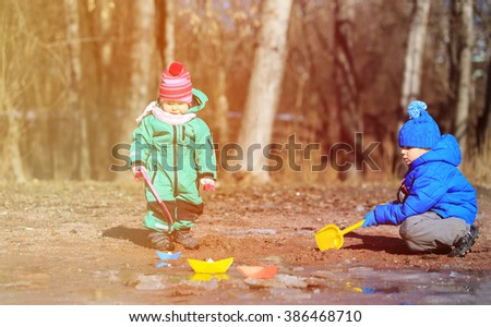 little boy and girl playing in spring - stock photo