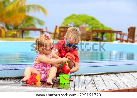 little boy and girl playing in swimming pool at the beach